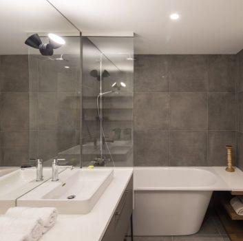 Biało-szara łazienka z wanną prostokątną, szafką z umywalką nablatową i lustrem na całości szafki
