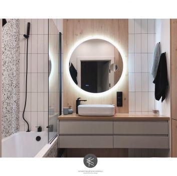Multikolorowa łazienka z wanną, białą szafką z umywalką nablatową oraz toaletą