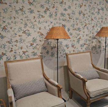 Beżowy salon z beżowymi fotelami oraz bambusowymi lampkami