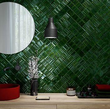 Zielona łazienka z okrągłym lustrem, czarną lampą oraz drewnianą szafką