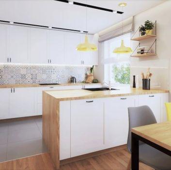 Biała kuchnia z białymi meblami, drewnianymi blatami oraz wyspą