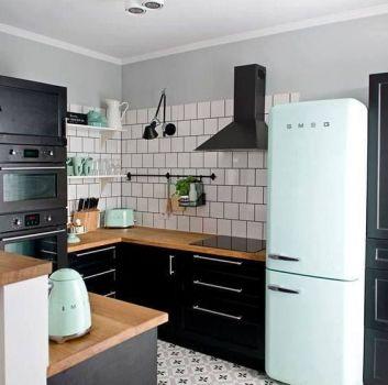 Szaro-biała kuchnia z czarnymi meblami, drewnianymi blatami i miętowymi dodatkami