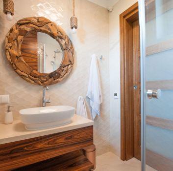 Beżowa łazienka z prysznicem, drewnianą półką z umywalką nablatową oraz drewnianym lustrem