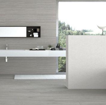 Beżowa łazienka z ścianą przed którą jest wanna a za którą jest biały blat z wbudowaną umywalką oraz duże okno