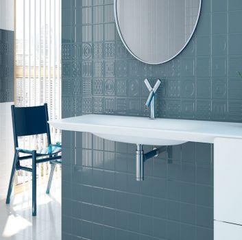 Niebieska łazienka z wbudowaną białą umywalką, białymi szafkami i okrągłym lustrem
