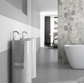 Szaro-biała łazienka z wanną wolnostojącą, dwoma umywalkami wolnostojącymi oraz przejściem do sypialni