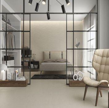 Szaro-biały salon z beżowym, skórzanym fotelem, drewnianym stoliczkiem oraz drewnianą półką