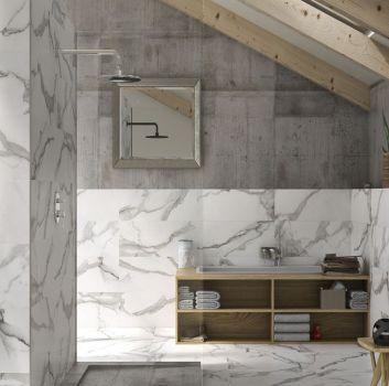 Szaro-biała łazienka z otwartym prysznicem przed którym jest ścianka z umywalką oraz drewnianą szafką a przed nimi duże, drewniane okno