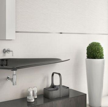 Biała łazienka z lustrzanym paskiem pośrodku ściany, oryginalną czarną umywalką i prostokątną półką nad nią