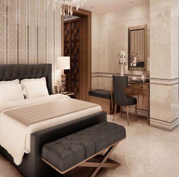 Beżowa sypialnia z grafitowym łóżkiem, przed którym stoi siedzisko, drewnianą toaletką z szarym krzesłem oraz przejściem do łazienki
