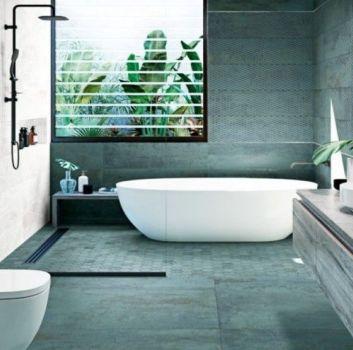 Biało-zielona łazienka z wanną wolnostojącą, toaletą oraz drewnianą szafką z umywalką nablatową