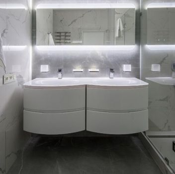 Biało-szara łazienka z dużym prysznicem, dwoma białymi szafkami z wbudowanymi umywalkami i prostokątnym lustrem nad nimi