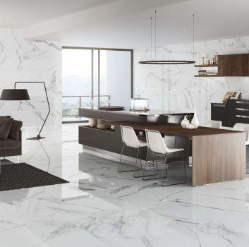 Biało-szary salon z czarną kanapą, dużym oknem oraz otwartą kuchnią