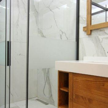 Biało-szara łazienka z prysznicem, toaletą oraz drewnianą szafką z wbudowaną umywalką