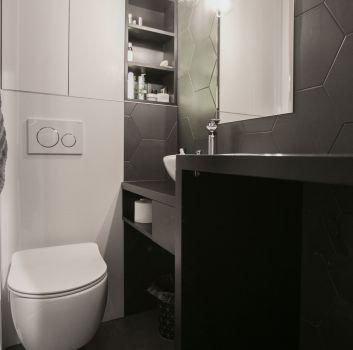 Biało-czarna łazienka z toaletą, grafitowym blatem z umywalką nablatową oraz prysznicem