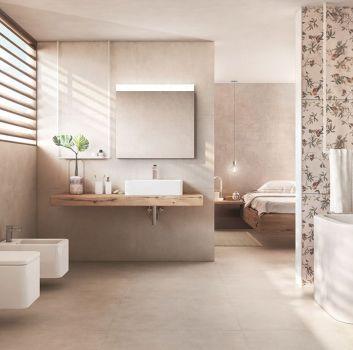 Beżowa łazienka z wanną wolnostojącą, toaletą oraz drewnianą szafką z umywalką nablatową