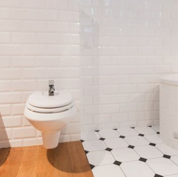 Biało-czarna łazienka z toaletą, bidetem i zabudowaną wanną
