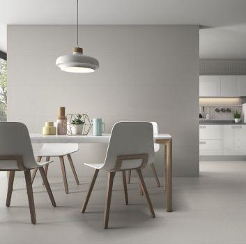 Szara kuchnia z białymi meblami, białym stołem z białymi krzesłami oraz dużymi oknami