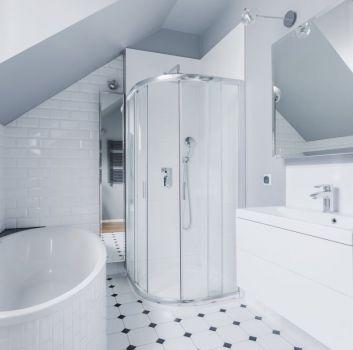 Biało-czarna łazienka z wanną, prysznicem oraz białą szafką z wbudowaną umywalką