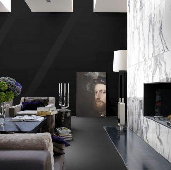 Grafitowy salon z nowoczesnym kominkiem, szarym kompletem wypoczynkowym z fioletowymi poduszkami oraz czarnym stolikiem