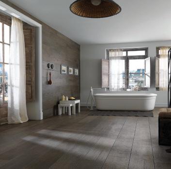 Szara łazienka z wanną wolnostojącą, dużą ilością okien oraz przedzieloną regałem sypialnią