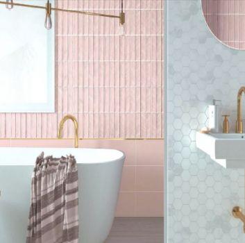 Różowa łazienka z wanną wolnostojącą, umywalką i okrągłym lustrem