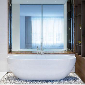 Biała łazienka z wanną wolnostojącą na kamieniach, toaletą oraz szafką z wbudowaną umywalką