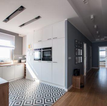 Szara kuchnia z białymi meblami, drewnianymi blatami oraz oknem