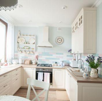 Pastelowa kuchnia z białymi meblami, oknem oraz jadalnią