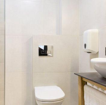 Beżowo-biała łazienka z prysznicem, toaletą i drewnianą szafką z umywalką nablatową i lustrem