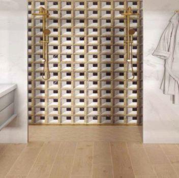 Beżowo-biała łazienka z dwoma prysznicami, białą szafką z dwoma umywalkami nablatowymi i dwoma złotymi lustrami