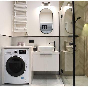 Szara łazienka z czarnym prysznicem, białą szafką z umywalką nablatową i obudowaną pralką