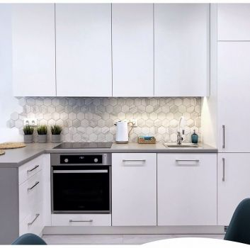 Biało-szara kuchnia z białymi meblami, białym stolikiem oraz niebieskimi krzesłami
