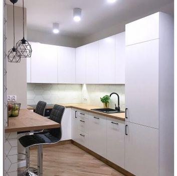 Biała kuchnia z białymi meblami, drewnianymi blatem z dwoma czarnymi hokerami oraz dużą ilością oświetlenia