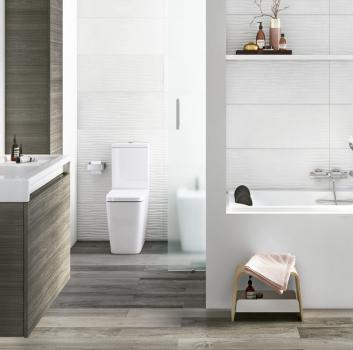 Biała łazienka z wanną wolnostojącą, schowaną za szybą toaletą oraz drewnianą szafką z wbudowaną umywalką