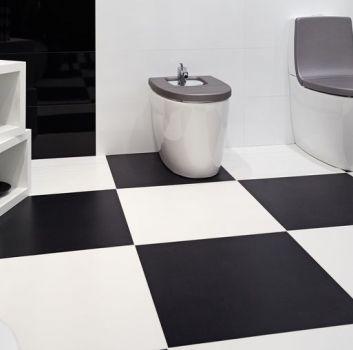 Biało-czarna łazienka z toaletą, bidetem oraz dwoma półkami