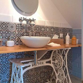 Biało-czarna łazienka z okrągłym lustrem, drewnianym blatem oraz umywalką nablatową