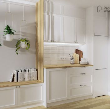 Biała kuchnia z białymi meblami, drewnianymi blatami oraz miejscem do siedzenia