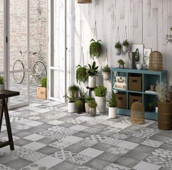 Szaro-biały salon z dużą ilością roślin, drewnianym stołem oraz wyjściem na taras
