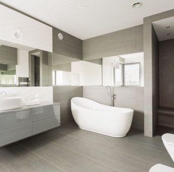 Biało-szara łazienka z oryginalnym prysznicem, wanną wolnostojącą i toaletą
