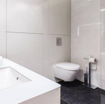 Biało-czarna łazienka z toaletą, prysznicem oraz wbudowaną umywalką