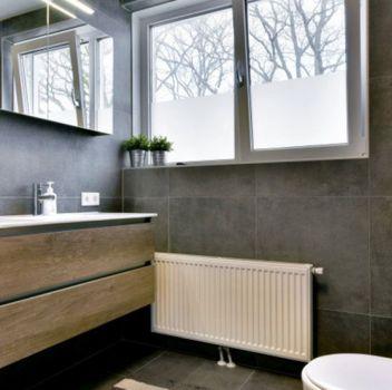 Czarna łazienka z drewnianymi meblami, toaletą oraz oknem