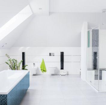 Biała łazienka z zabudowaną płytkami wanną, toaletą oraz dużym prysznicem