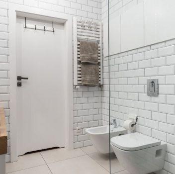 Biała łazienka z prysznicem, toaletą oraz drewnianym blatem z umywalką nablatową