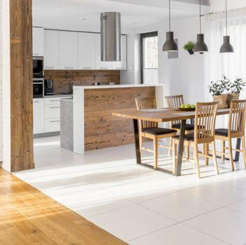 Biała kuchnia z białymi meblami, jadalnią z drewnianym stołem i krzesłami oraz drewnianymi schodami