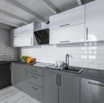 Biała kuchnia z grafitowo-białymi meblam i drewnianymi belkami na suficie