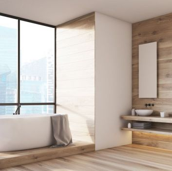 Beżowa łazienka z wanną wolnostojącą na podeście, drewnianym blatem z dwoma umywalkami nablatowymi oraz dwoma lustrami