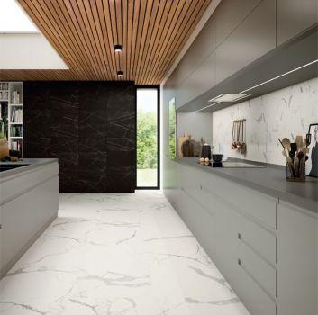 Biało-czarna kuchnia z szarymi meblami, wyspą oraz wąskim oknem