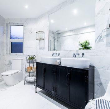 Biała łazienka z toaletą, wanną oraz drewnianą szafką z dwoma umywalkami nablatowymi