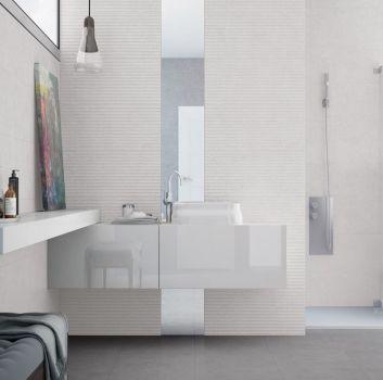 Biała łazienka z białymi blatami, prysznicem oraz wanną wolnostojącą